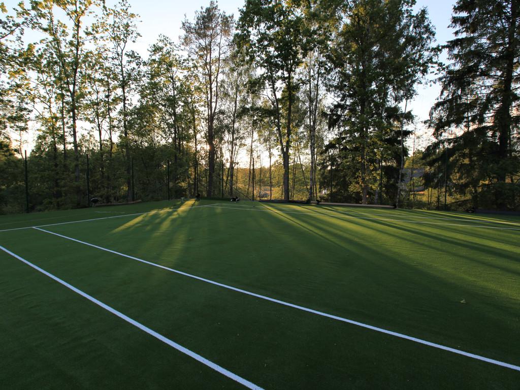 Tennisbana i anslutning till lekpark på andra sidan sjön