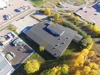 Gräsbelagd yta på byggnadens baksida som kan asfalteras och frigöra fler p-platser och uppställningsyta