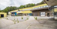 Del av asfalterad logistikyta med flertalet industriportar och lastkajer